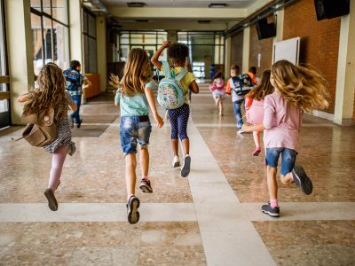 Back view of elementary students running in the school hallway.