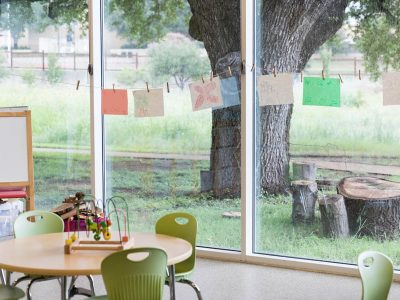 A tidy preschool or kindergarten classroom is prepared for students. A large window wall looks out on a large tree and tree stump.