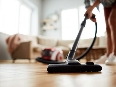 Close-up of unrecognizable woman using modern powerful hoover while vacuuming floor at home