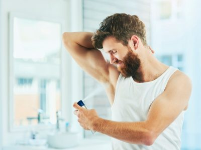 Cropped shot of a handsome young man spraying himself with deodorant