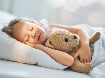 Adorable little child is sleeping in the bed with her toy. The girl is hugging the teddy bear.