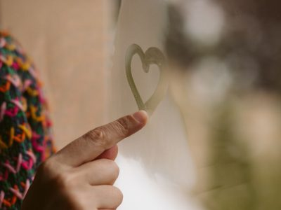 Beautiful girl hand drawing hearts in the window. Love and solitude concept.