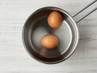 Two eggs in the water in a metal pan on the table  top view