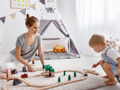 happy family mother and child son playing together in toy railway in playroom