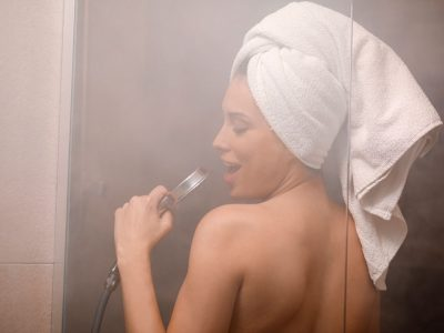 Singing in the shower. Natural Beauty Portrait beautiful young woman with a towel wrapped around her hair, after showering. In the bathroom.